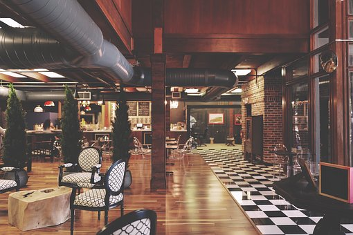 Interior of one of the most decadent hotel restaurants with dark wood furnishings and monochrome checker board floor.